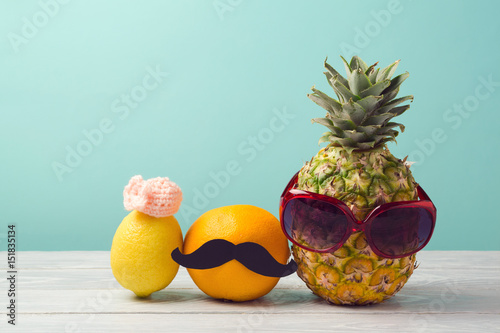 Pineapple, grapefruit and lemon over mint background. Party funny charactes. Tropical summer vacation concept