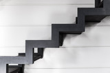 Stairs made of black metal over white wall - 151841107