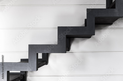 Stairs made of black metal over white wall