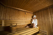 Young woman wrapped in a white towel relaxing in wooden sauna room