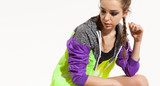 Beautiful young woman in a sporty bright jacket is resting after a workout. Portrait on a white background with free space on the left