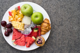 Top view of fruit plate by over concrete floor background. Exotic summer diet. Tropical beach lifestyle.