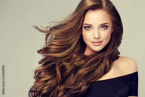Leinwanddruck Bild Brunette  girl with long  and   shiny wavy hair .  Beautiful  model with curly hairstyle .