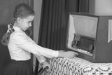 Little girl listens to old radio.