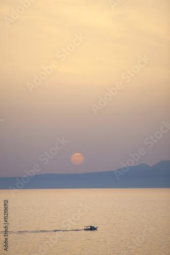 fishing boat on sea near greek shore during colorful sundown