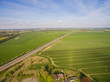 Aerial view of green agricultural fields with a country road and a smal city under blue sky in germany