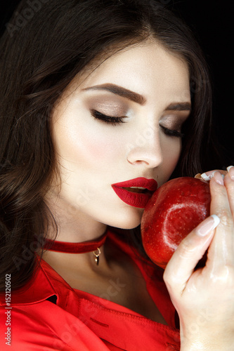 Beautiful woman portrait with nice make up, red lips and red apple in hands Poster
