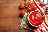 Delicious ketchup in bowl with ingredients on wooden background, top view