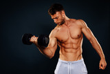 Attractive fitness man holding dumbbells in the hands in studio