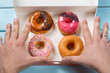 Постер, плакат: Hands are ready to take donuts out of the box with colorful donuts on blue wooden background Top view Unhealthy food concept
