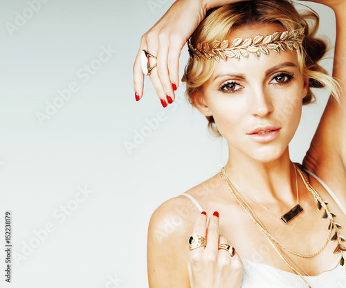 young blond woman dressed like ancient greek godess, gold jewelr