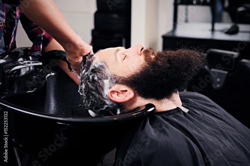 Hairdresser washing bearded men's hair. © Fxquadro