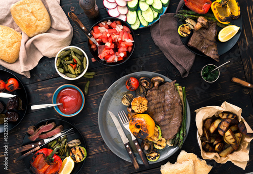Grilled steak and grilled vegetables on wooden table - 152253392