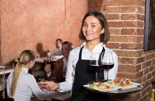 Adult female waiter showing country restaurant