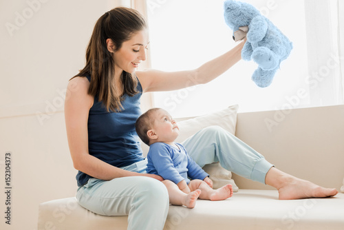 Beautiful mother and her son playing with teddy bear. Young family concept