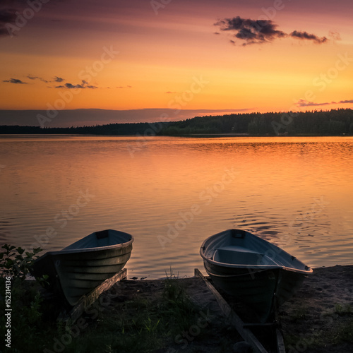 Papiers peints Orange eclat Landscape with lake, boats and sunset at summer evening in Finland