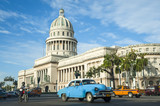 Brightly colored classic American cars serving as taxis pass on the main street in front of the Capitolio building in Central Havana, Cuba