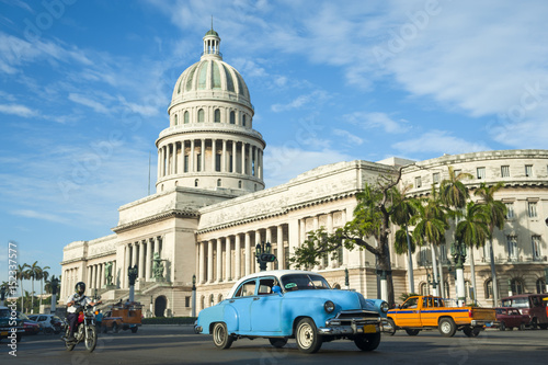 Fotobehang Havana Brightly colored classic American cars serving as taxis pass on the main street in front of the Capitolio building in Central Havana, Cuba