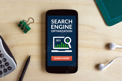 Search Engine Optimization (SEO) concept on smart phone screen on wooden desk Poster