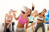 Group of happy people with coach dancing in gym - 152353361