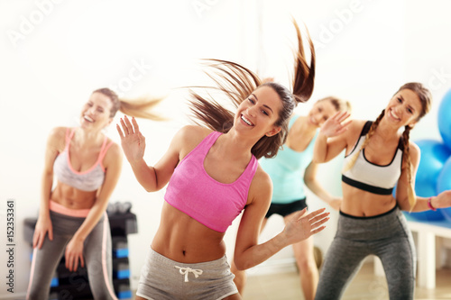 Wall mural Group of happy people with coach dancing in gym