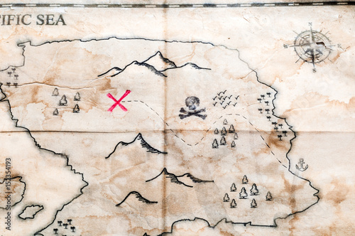 Close up to Vintage folded fake map with red cross of Pirates Treasure chest