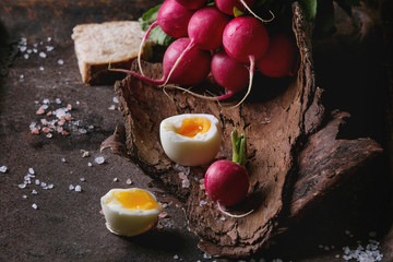 Rustic lunch breakfast with fresh young vegetables radish, soft boiled egg, salt and bread on wooden bark over dark texture metal background. Close up. Healthy eating