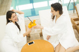 Two young ladies clothed bathrobe lying down the spa