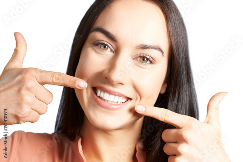 Attractive Woman Pointing To Her Smile With Perfect White Teeth