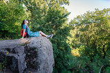 girl sits on a rock in the forest