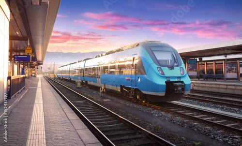 Piękny widok z nowożytnym wysokim prędkość pociągiem na staci kolejowej i kolorowy niebo z chmurami przy zmierzchem w Europa. Przemysłowy krajobraz z niebieskim pociągiem na platformie kolejowej. Tło kolejowe