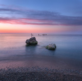 Amazing sunrise at the sea. Beautiful landscape with blue water, stones and colorful sky with clouds in summer morning. Seascape. Tranquil scene. Nature background