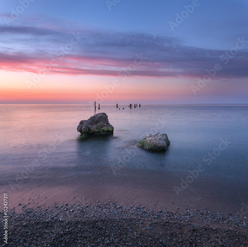 Tuinposter Aubergine Amazing sunrise at the sea. Beautiful landscape with blue water, stones and colorful sky with clouds in summer morning. Seascape. Tranquil scene. Nature background