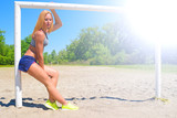 Beautiful fitness girl on the background of a football goal the sun shines brightly.