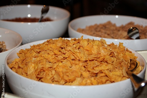 A white bowl filled with cereal, sideview A ceramic bowl of cereal ready for breakfast to start everyone's day.