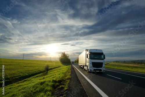 biala-ciezarowka-jazdy-na-drodze-asfaltowej-miedzy-polami