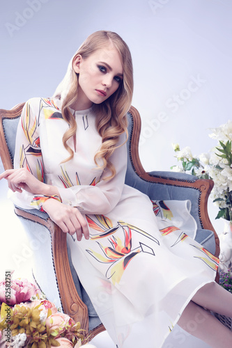 Fashion portrait of young blond woman with flowers.