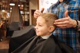 Nice pleasant hairdresser holding the boys head