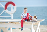 Handsome boy teen happyly spending time together with his friend bulldog on sea side Kid dog holding playing two sea stars close to life buoy float wearing red pants trousers slippers and t-shirt - 152607313