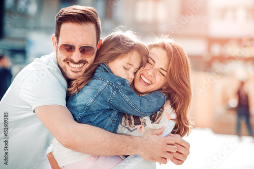 Happy young family in city street