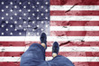 Top view of a man standing on damaged cracked cement floor painted with Usa flag. Point of view perspective used. Conceptual United States of America disintegration background.