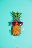 Fashion pineapple with sunglasses and headphones listens to music over blue background