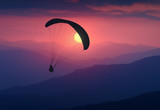 Silhouette of flying paraglide in a light of sunrise