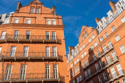 Opulent restored elegant Victorian period building in red bricks and white windo Poster