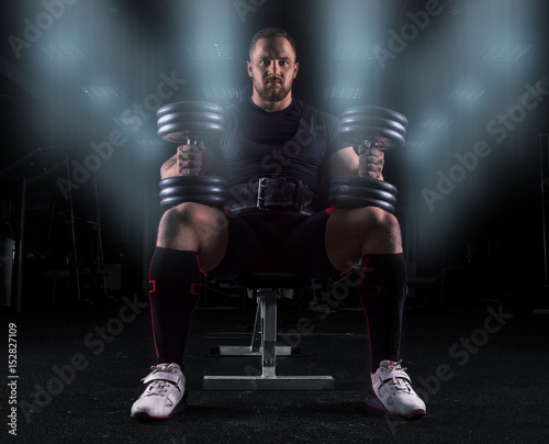 Professional weightlifter sits on a bench with two dumbbells on his lap