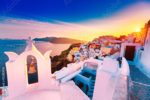 Classical view at sunset over chapel in Oia (Ia) village on Santorini volcano island in Greece. Breathtaking epic sunset scenery. Popular travel tourist destination for romantic trip.