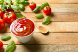 Delicious ketchup with basil and tomatoes on wooden background