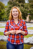 Simple american girl from next door in a plaid shirt walk in central park. Smiling and laughing have fun time - 152945113