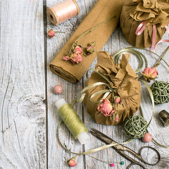 Creativity Packing gifts in vintage style with the use of natural materials.  Paper, decorative tape, dried flowers, threads and scissors on a gray wooden background.  © elizaveta66