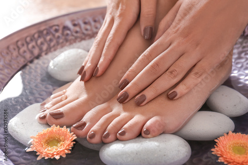 Female feet and hands with brown manicure on spa stones, closeup © Africa Studio